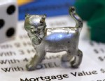 PHOTO: The newest Monopoly token, a cat, rests on a Boardwalk deed next to a die and houses at Hasbro Inc. headquarters, in Pawtucket, R.I., Feb. 5, 2013.