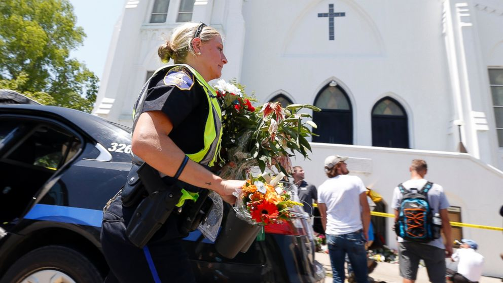 Charleston police officer T. Graves carries flowers, June 18, 2015 to a make-shift memorial in front of the Emanuel AME Church in Charleston, S.C.