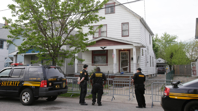 PHOTO: Sheriff deputies stand outside a house in Cleveland, May 7, 2013, the day after three women who vanished a decade ago were found there.