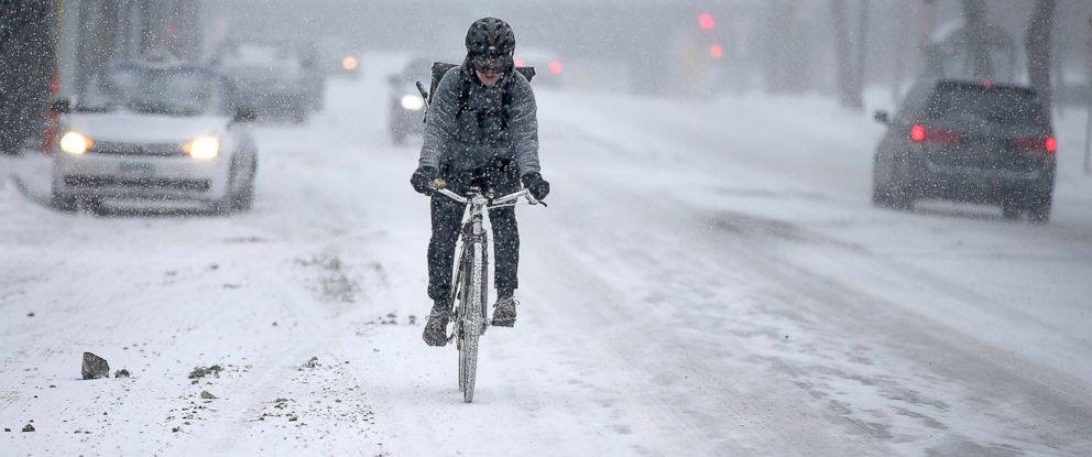PHOTO: A cyclist pedals through traffic through winter weather conditions on Jan. 8, 2015 in Minneapolis, Minn.