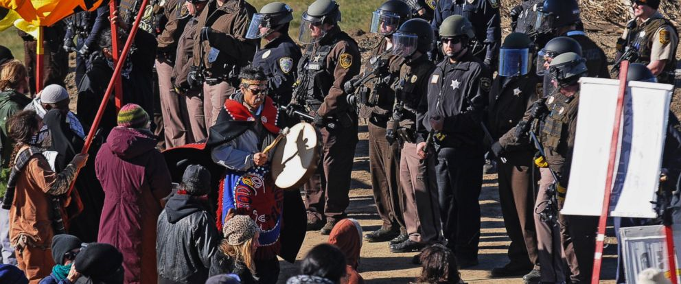PHOTO: A person with a hand drum paces between law enforcement officers and a line of protesters along North Dakota Highway 6, south of St. Anthony, North Dakota,Oct. 10, 2016.