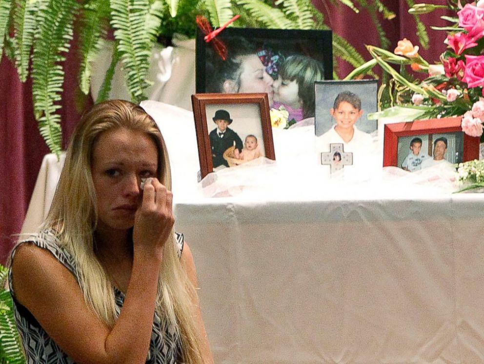 PHOTO: Mourners look at a display of photos during a memorial service at Bell High School for the victims of Thursdays shootings on Sunday, Sept. 21, 2014 in Bell, Fla.