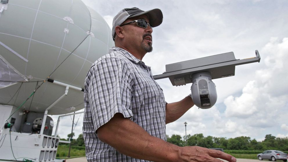 In this June 26, 2014 photo, Rob King shows off the sensor that attaches to the bottom of a surveillance blimp, a large helium balloon that has cameras attached, at Ohio/Indiana Unmanned Aircraft Systems Center in Clintonville, Ohio.