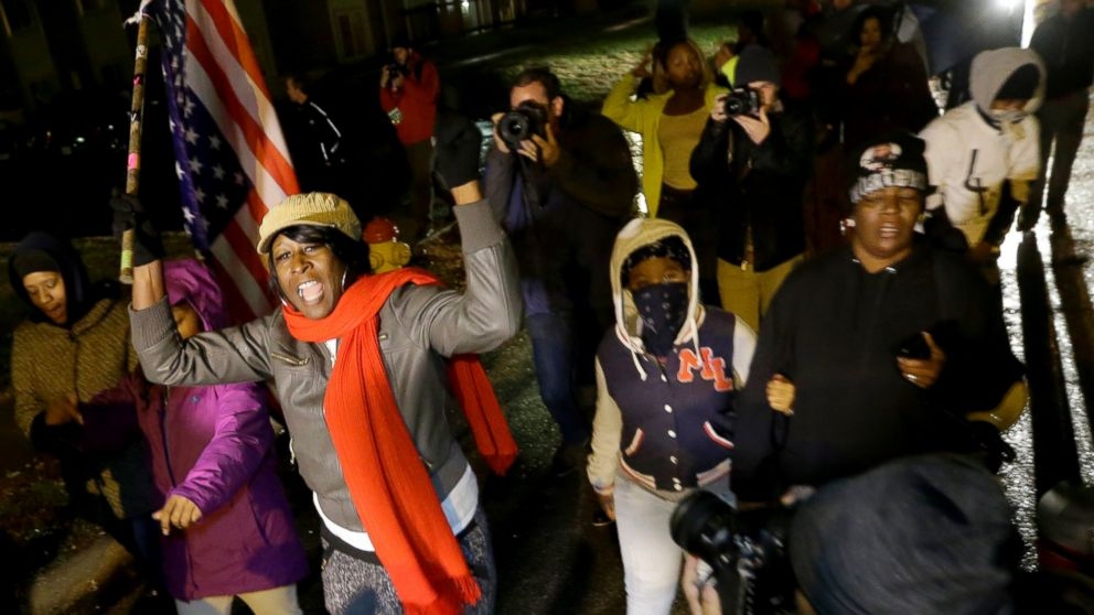 Protesters march Saturday, Nov. 22, 2014, along a stretch of road where violent protests occurred following the August shooting of unarmed black teenager by a white police officer in Ferguson, Mo.