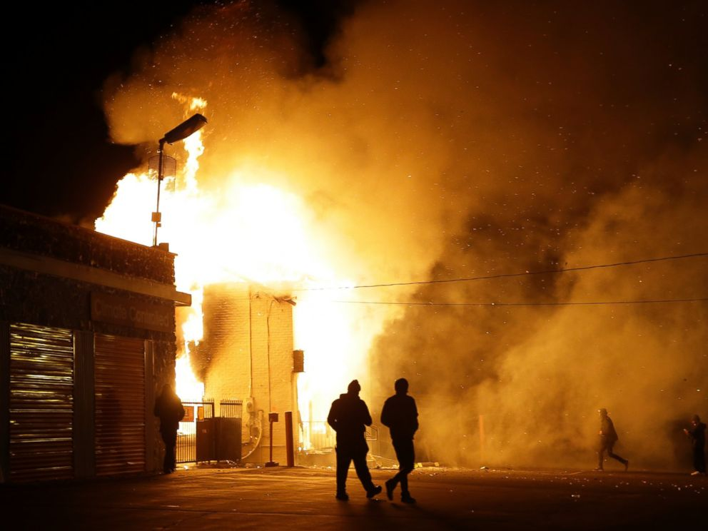 PHOTO: People walk away from a storage facility on fire after the announcement of the grand jury decision, Nov. 24, 2014, in Ferguson, Mo.