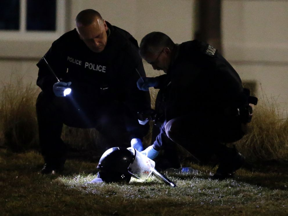 PHOTO: Police shine a light on a helmet as they investigate the scene where two police officers were shot outside the Ferguson Police Department, March 12, 2015, in Ferguson, Mo.