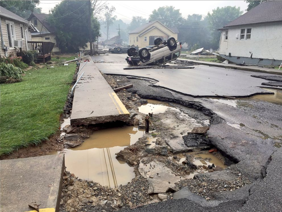 PHOTO: Overturned vehicles sit on a heavily damaged road after flooding near White Sulphur Springs, W.Va., Friday, June 24, 2016.