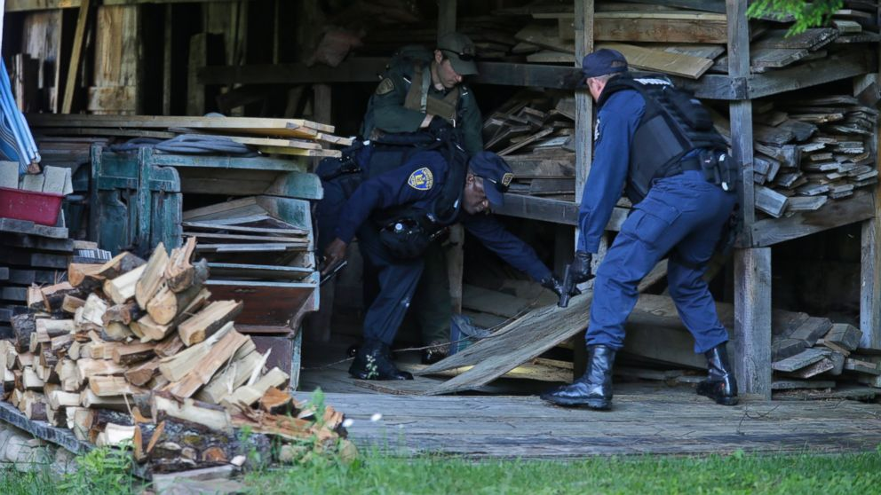 New York State Department of Corrections Officers and a forest ranger search a barn in Owls Head, N.Y. for convicted murderers Richard Matt and David Sweat, June 26, 2015.