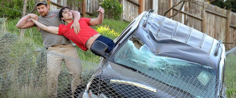 PHOTO: An unidentified passer-by pulls the driver from a SUV to safety after the vehicle traveled downhill and was stopped by a chain link fence just short of a 30-foot vertical drop onto the Bryden Canyon Road, April 15, 2015, in Lewiston, Idaho.