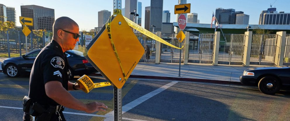 PHOTO: A police officer puts up yellow tape to close the school outside of Edward Roybal High School in Los Angeles, Dec. 15, 2015.