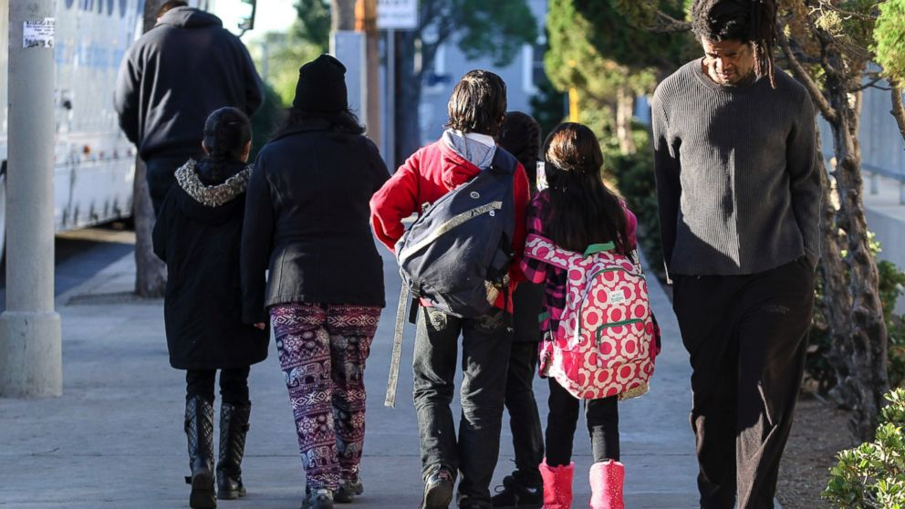 Parents take their children home from school early, Dec. 15, 2015, in Los Angeles.