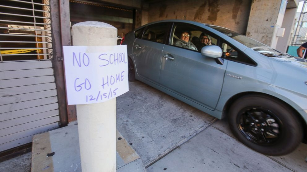 """A vehicle leaves the Miguel Contreras Learning Complex past a sign that reads """"No School Go Home,"""" Dec. 15, 2015, in Los Angeles."""
