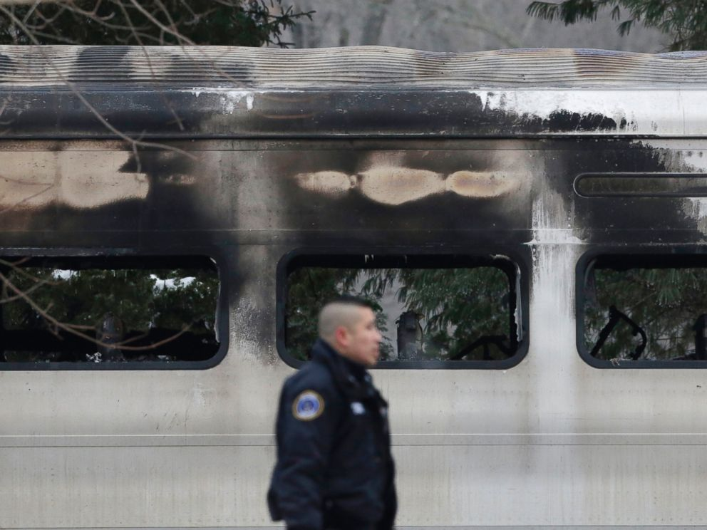 PHOTO: A police officer walks by burned and blackened windows of a Metro-North train stopped on the tracks, on Feb. 4, 2015, in Valhalla, N.Y.