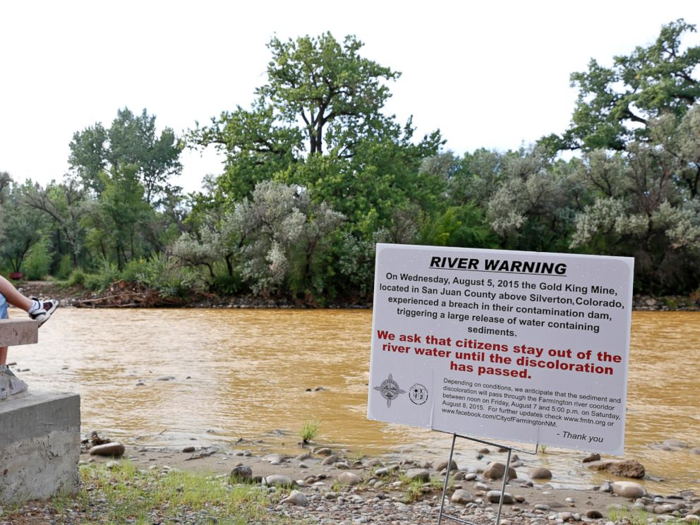 PHOTO: A warning sign from the city is displayed in front of the Animas River as orange sludge from a mine spill upstream flows past Berg Park in Farmington, N.M., Aug. 8, 2015.