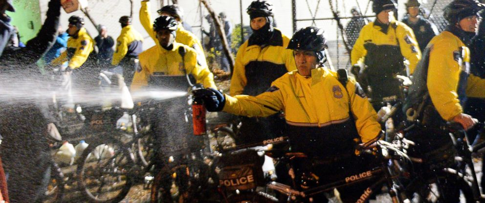 PHOTO: A police officer sprays a liquid towards demonstrators at the Minneapolis Police Department 4th Precinct building, Nov. 18, 2015, in Minneapolis.
