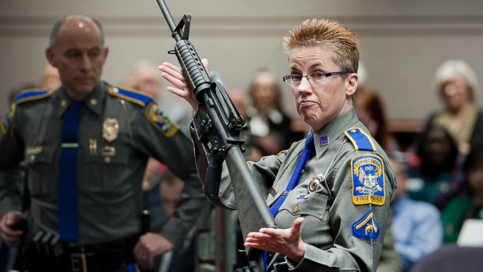 Detective Barbara J. Mattson of the Connecticut State Police holds up a Bushmaster AR-15-style rifle, the same make and model of gun used by Adam Lanza in the Sandy Hook School shooting at the Legislative Office Building in Hartford, Conn., Jan. 28, 2013.
