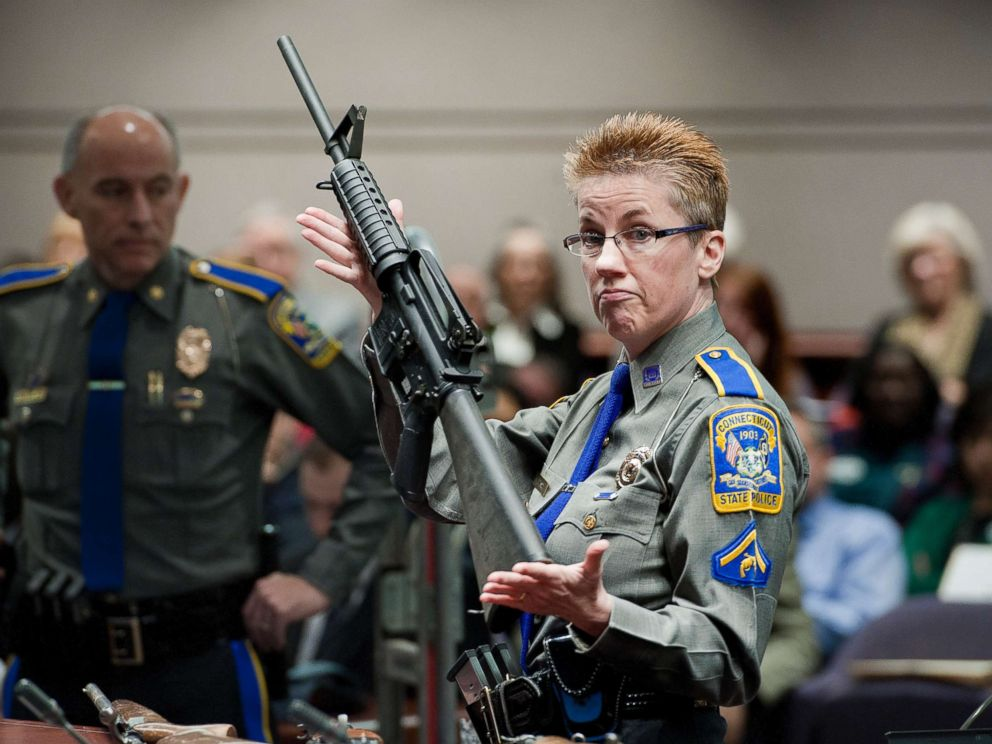 Police officer holds up a Bushmaster AR-15-style rifle the same make and model of gun used by Adam Lanza in the Sandy Hook School shooting at the Legislative Office Building in Hartford Conn. Jan. 28 2013