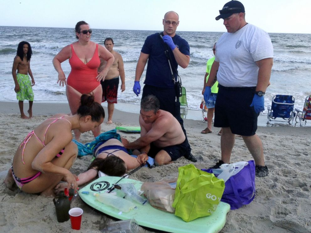 PHOTO: People assist a teenage girl at the scene of a shark attack in Oak Island, N.C., June 14, 2015.