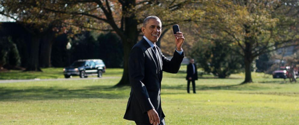 PHOTO: President Barack Obama holds up his BlackBerry after he forgot it and returned back to the White House to retrieve it before his departure in Washington, Nov. 21, 2014, to Andrews Air Force Base, Md.