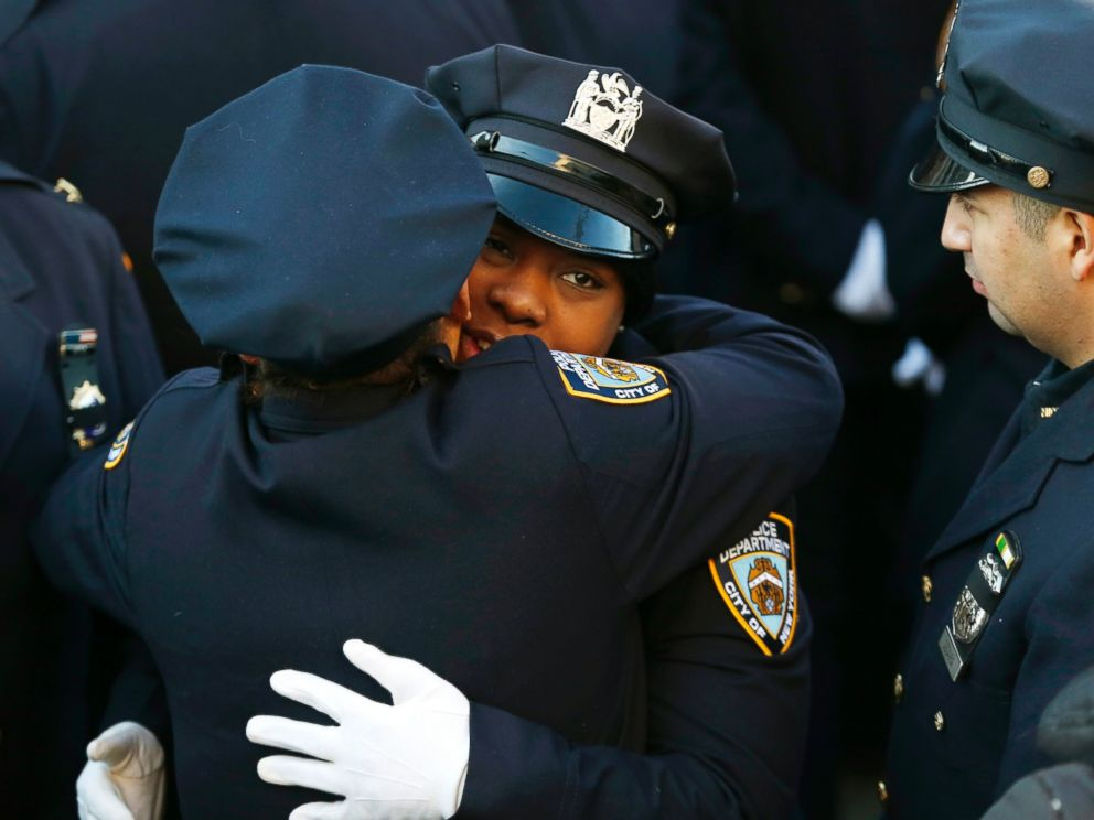 PHOTO: New York City police officers embrace outside of Christ Tabernacle Church, in the Glendale section of Queens, before funeral services for officer Rafael Ramos, Saturday, Dec. 27, 2014, in New York.