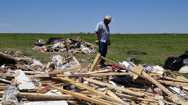 PHOTO: John Chapman looks over what little is left of his daughter Lauren Porters double wide that was picked up and strewn over a cattle pasture by a tornado, Saturday June 1, 2013 in El Reno Okla.