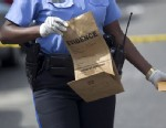 PHOTO:New Orleans police officer collects evidence at the scene of a shooting at the intersection Frenchman Street at N. Villere on Mothers Day in New Orleans, Sunday May 12, 2013.