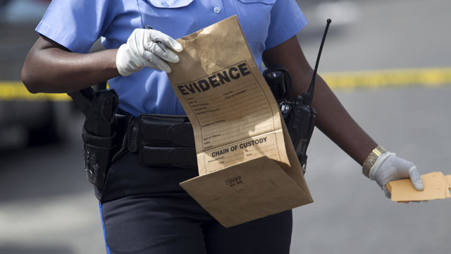 PHOTO: New Orleans police officer collects evidence at the scene of a shooting at the intersection Frenchman Street at N. Villere on Mothers Day in New Orleans, Sunday May 12, 2013.