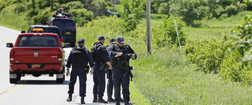 PHOTO: A heavily armed law enforcement officer patrols the edge of road during a search for two escaped killers in Boquet, N.Y., June 9, 2015.