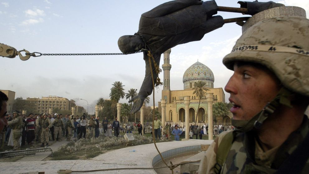 The April 9, 2003 file photo shows Iraqi civilians and U.S. soldiers pulling down a statue of Saddam Hussein in downtown Baghdad.