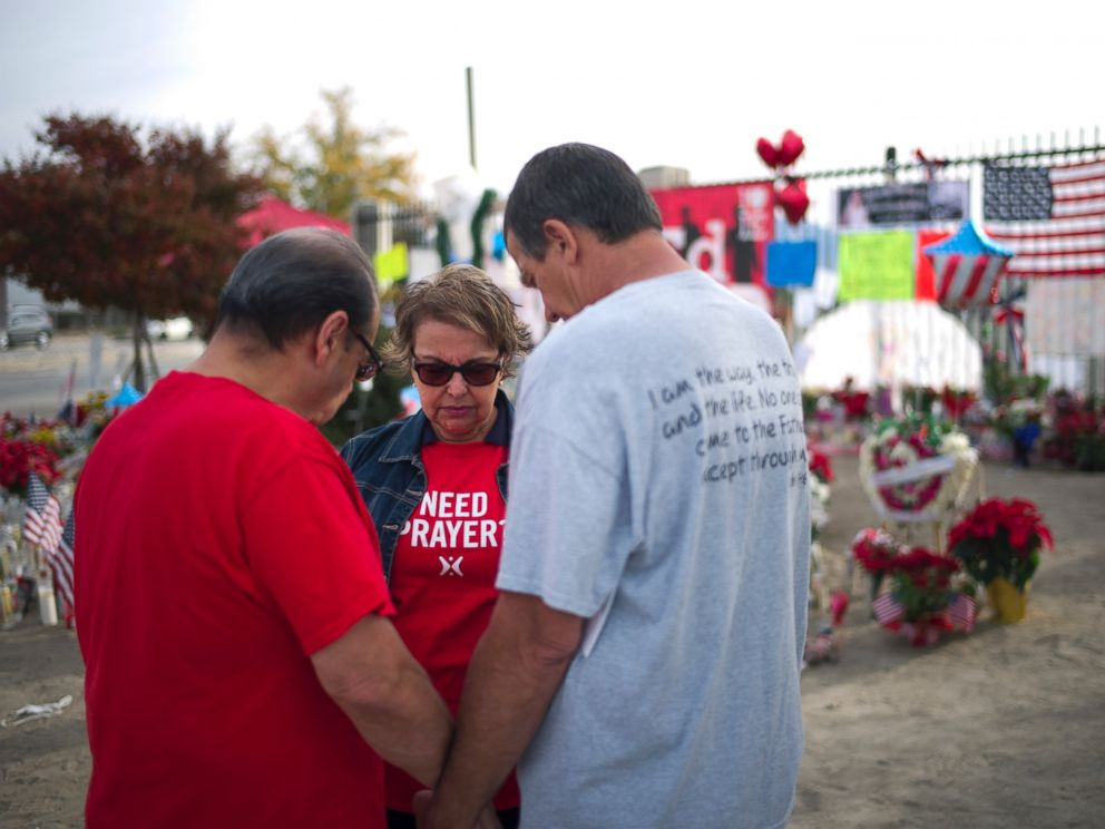 PHOTO: Ray Molina, from left, Molinas wife, Yvonne, and Leonard Lynch pray at a makeshift memorial set up near the Inland Regional Center, the site of a fatal shooting that killed 14 people, Dec. 9, 2015, in San Bernardino, Calif.