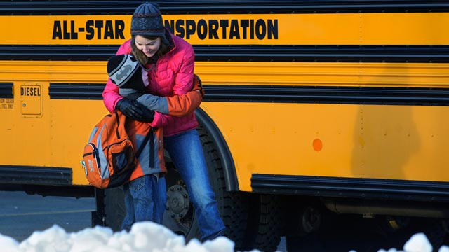 PHOTO: A woman hugs a child before he boards a bus on the first day of classes after the holiday break, in Newtown, Conn., Jan. 2, 2013.