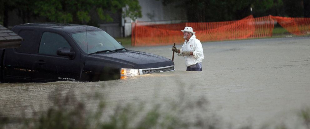 PHOTO: A man watches as a vehicle tries to navigate flood waters in Florence, S.C., Sunday, Oct. 4, 2015 as heavy rains continue to saturate the state, causing widespread flooding.