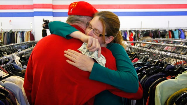 PHOTO: A woman hugs a Secret Santa after getting a $100 dollar bill from the wealthy philanthropist from Kansas City, Mo. while looking for clothes at the Salvation Army store in Staten Island, New York, Nov. 29, 2012.