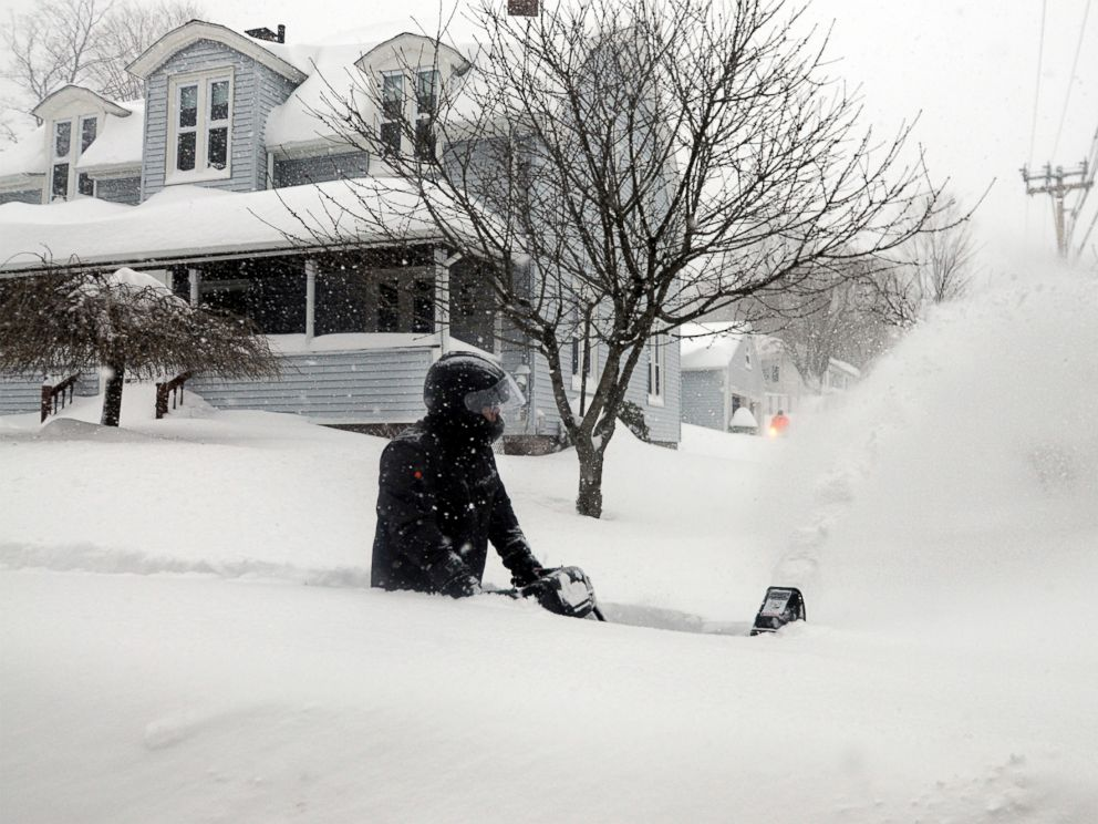 PHOTO: John Slasell wades through waist-deep snow as he snow blows the sidewalk along Slater St. in Webster, Mass.