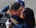 PHOTO: Army Sgt. First Class Eric Pazz kisses his wife Miriam as his son Eric Jr. watches during the 124th Rose Parade in Pasadena, Calif., Jan. 1, 2013.