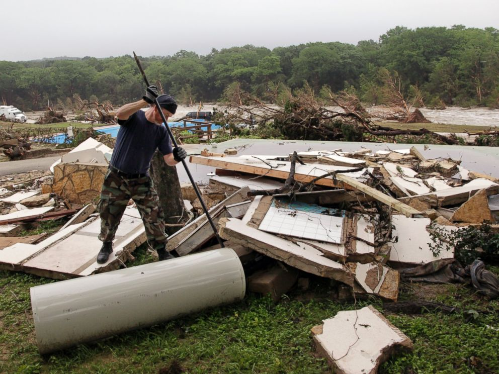 PHOTO: Kevin Calaway pries apart debris from a cabin shattered from a flood at a resort along the Blanco River, May 26, 2015, in Wimberley, Texas.