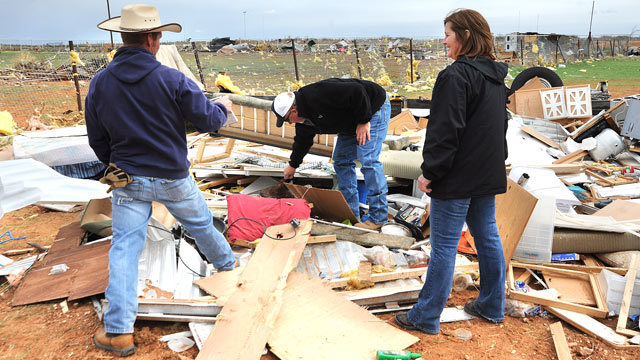 PHOTO: People search through debris after a storm passed through Gardendale, Texas, March 19, 2012.