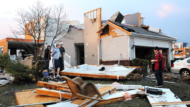 PHOTO: Residents move belongings out of a house on the corner of Meadow View and York St. in Huron Farms neighborhood of Dexter, Mich., March 15, 2012 after a tornado struck their home.