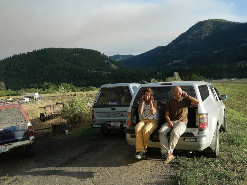 PHOTO: Steve and Nancy Morse talk on their phones as they watch a wildfire burn above their home on Twisp River Road in Twisp, Wash., Aug. 19, 2015.