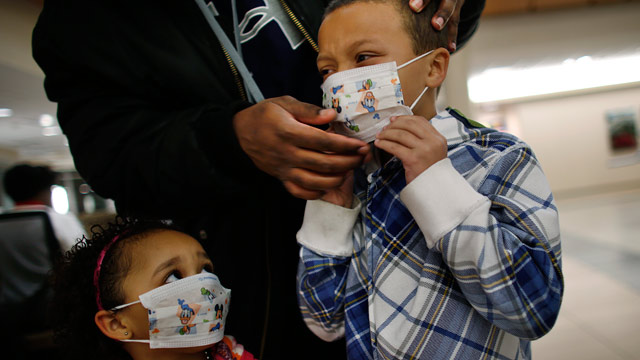 PHOTO: Damien Dancy puts masks on his children Damaya, 3, left, and Damien, 7, on Wednesday, Jan. 9, 2013 at Sentara Princess Anne Hospital in Virginia Beach, Va.