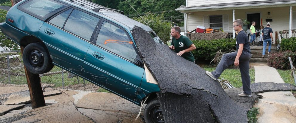 PHOTO: Jay Bennett, left, and step-son Easton Phillips survey the damage to a neighbors car in front of their home damaged by floodwaters as the cleanup begins from severe flooding in White Sulphur Springs, W. Va., June 24, 2016.