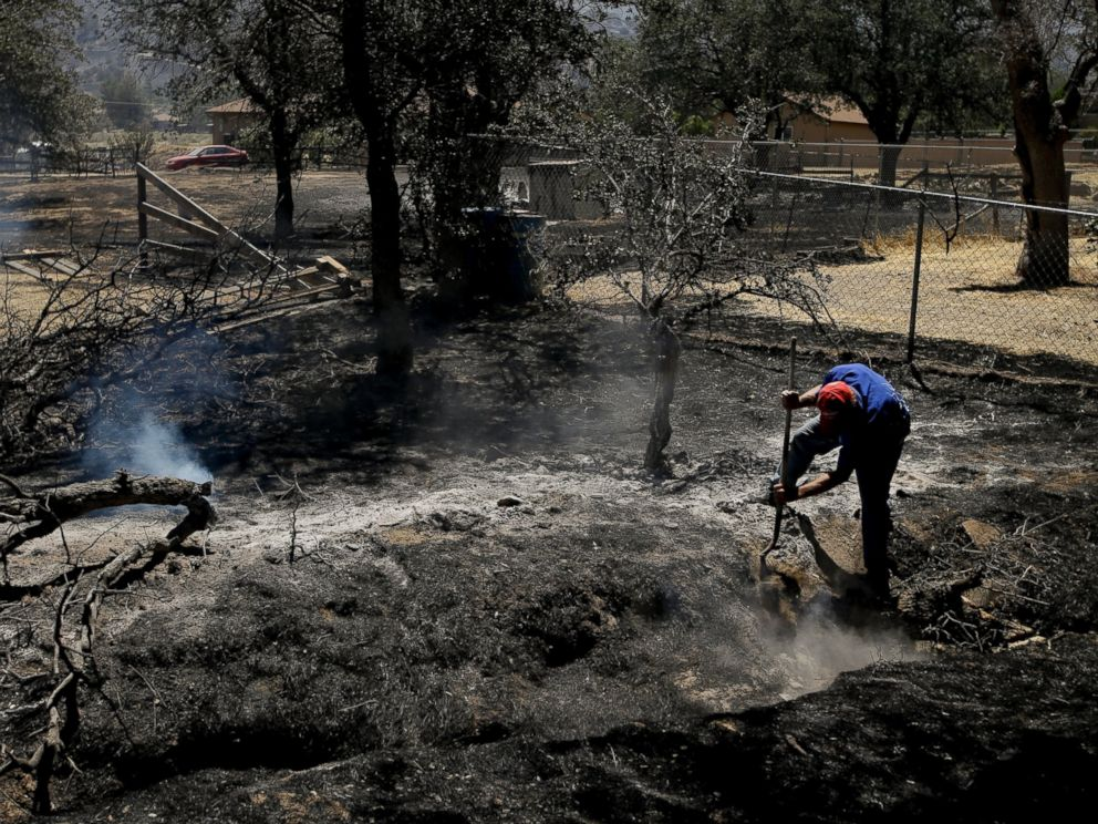 PHOTO: Alan Germain puts out hotspots on his neighbors property destroyed by a wildfire, June 24, 2016, near Lake Isabella, Calif.