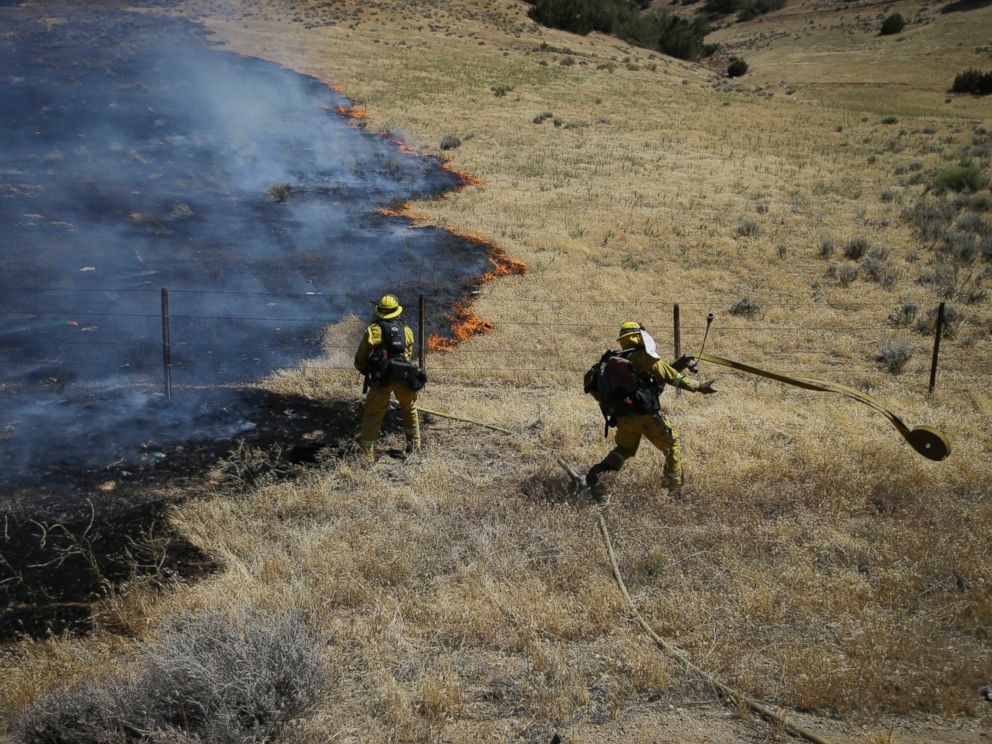 PHOTO: Firefighters prepare water hoses to battle a wildfire burning along Highway 178 near Lake Isabella, Calif., June 24, 2016.