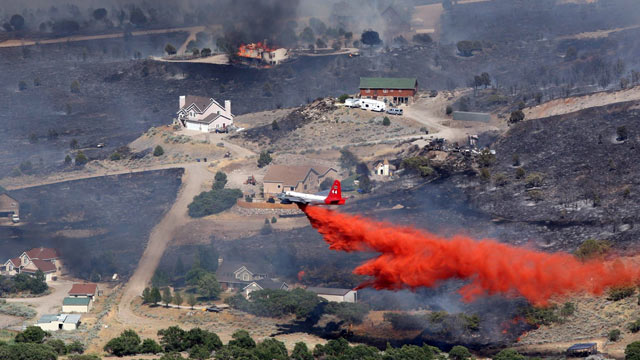 PHOTO: An air tanker drops retardant on a fire after it engulfed homes in the Rose Canyon area of Herriman, Utah, June 29, 2012.
