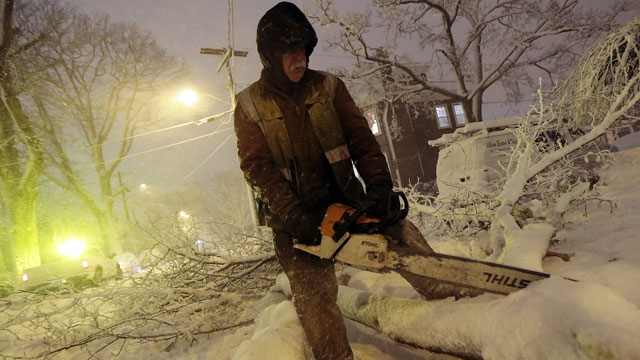 PHOTO:Louie Rodriguez of the New Bedford Forestry Department cuts a fallen tree at the intersection of Rotch St. and Maple St. in New Bedford, Mass., on Friday, Feb. 8, 2013, after heavy snow and winds from a storm.