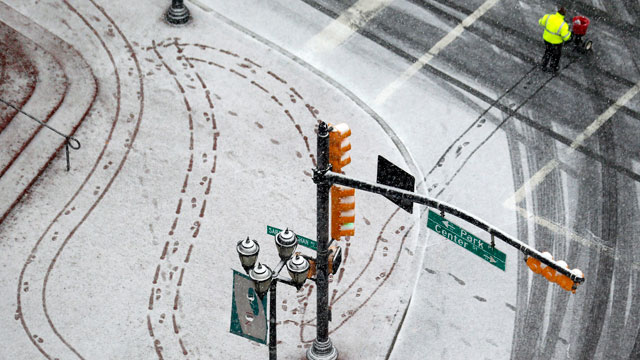 PHOTO: A person pushes a cart to spread salt on a snowy sidewalk at Military Park in downtown Newark, N.J. on Dec. 26, 2012.