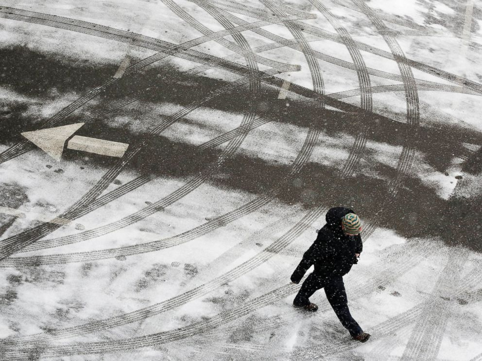 PHOTO: A pedestrian crosses a snowy parking lot before heavy snowfall arrives, Jan. 26, 2015, in New York.