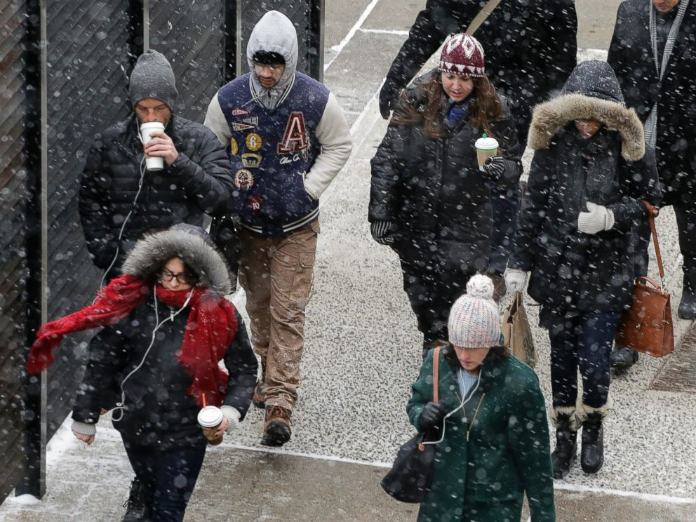 PHOTO: A light snow falls on pedestrians in New York, Jan. 26, 2015.