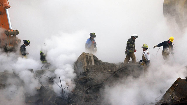 PHOTO: In this Oct. 11, 2001 file photo, firefighters make their way over the ruins and through clouds of smoke at the World Trade Center in New York.