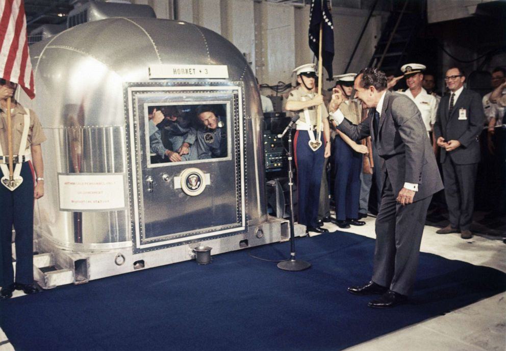 PHOTO: In this July 24, 1969, file photo, President Richard Nixon gives an OK sign as he greets Apollo 11 astronauts Neil Armstrong, Michael Collins, and Buzz Aldrin in a quarantine van aboard the USS Hornet.